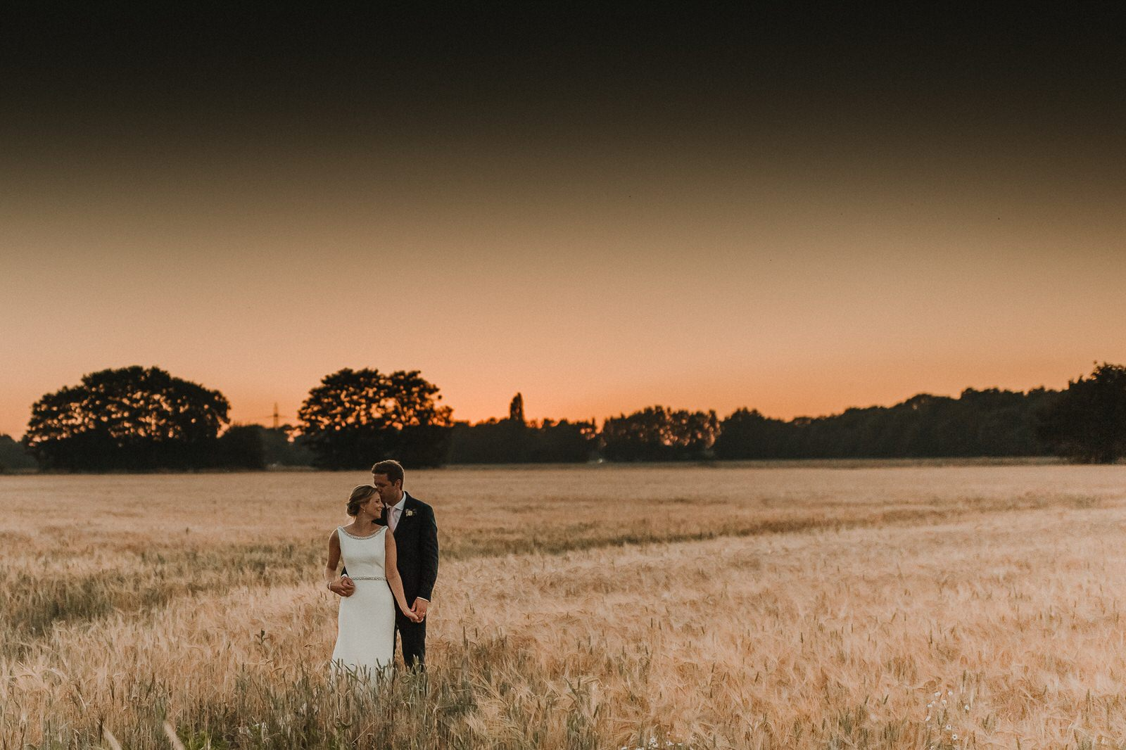 couple standing in a wheat field holding hands