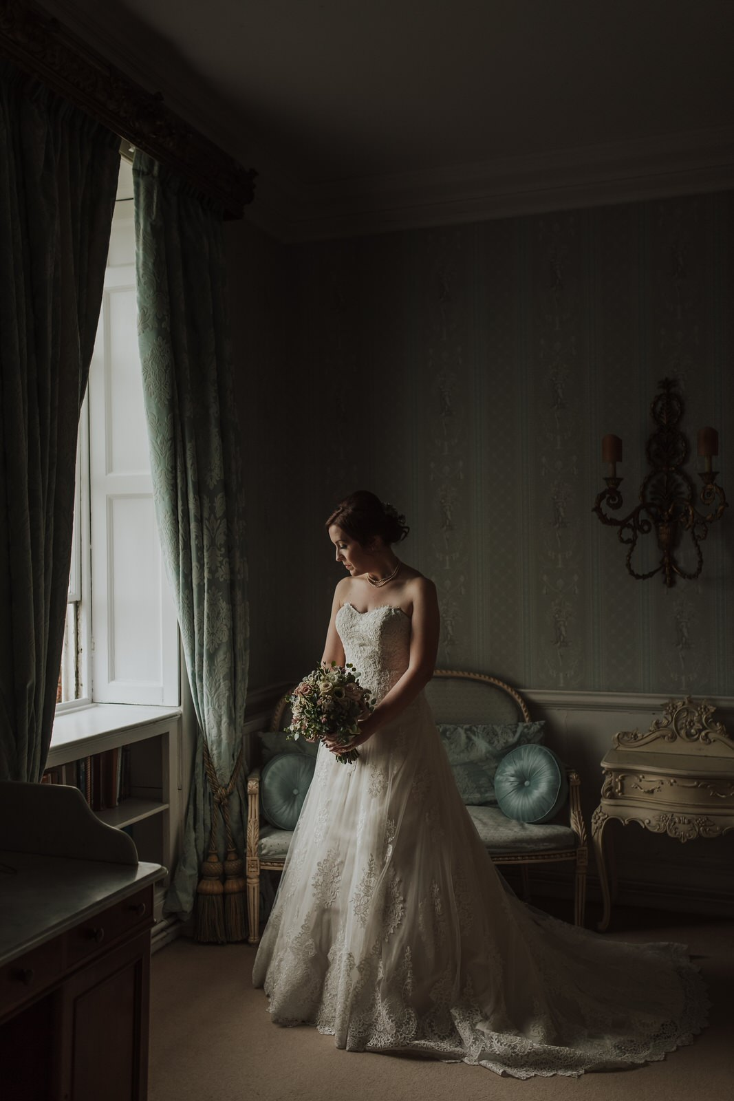 bride standing with bouquet in beautiful window light at Norwood Park